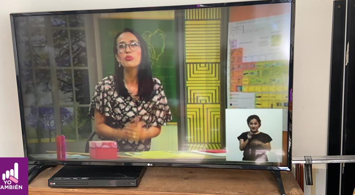 Fotografía de un televisor con uno de los programas de aprende en casa, dentro de el se alcanza a ver a una maestra y en la esquina inferior izquierda una Mujer realizando la interpretación del contenido a lengua de señas mexicana