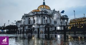 Fotografia de palacio de bellas artes, al frente de la fotografía se alcanza a ver un charco de agua y detrás el palacio nacional, no se alcanza a ver gente alrededor y se ve que es una tarde nublada