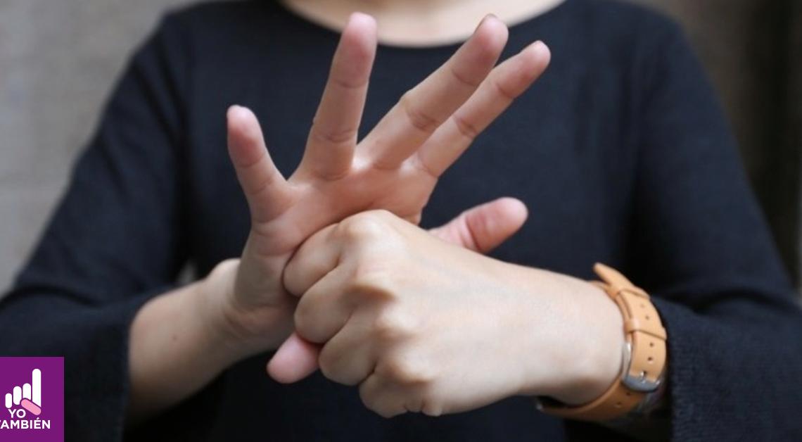 Fotografía de las manos de una mujer haciendo la seña de covid 19