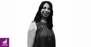 Fotografía de Adriana Pérez sonriendo hacia la camara, tiene una blusa sin mangas y el cabello suelto