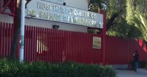 Fotografía de la entrada del hospital siquiatrico samuel ramirez, donde alcanzamos a ver la entrada cerrada y el nombre del hospital sobre la puerta, la reja que cubre la entrada esta hecha de muchos tubos de metal uno junto al otro y frente a ellos una fila de arbustos