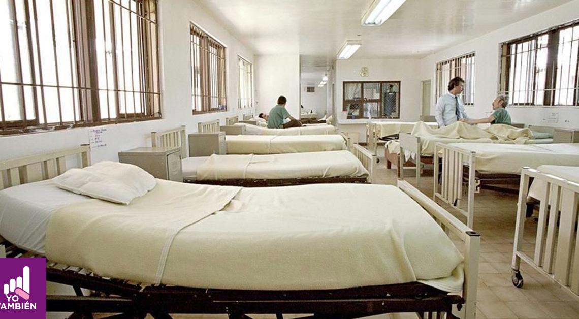 Fotografía de uno de los cuartos de un hospital siquiatrico donde se alcanza a la izquierda de la foto una linea de camas vacías y al final una persona sentada junto a la última cama mientras a la derecha hay otra fila de camas y en una de las últimas se alcanza a ver a un doctor platicando con otra persona