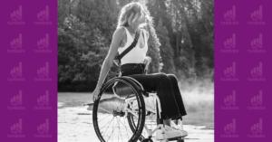 Fotografía de una mujer en silla de ruedas, tiene las manos sobre las ruedas y mira hacia la derecha