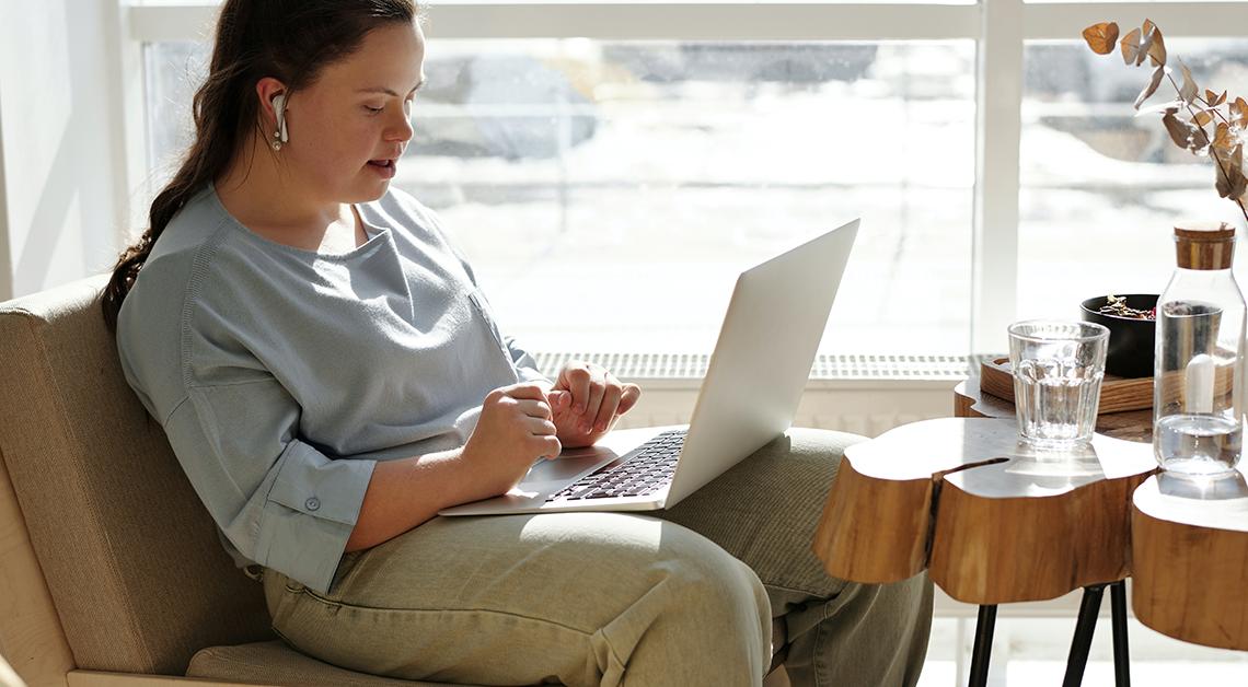 Fotografía de una mujer con síndrome de down sentada con una laptop en las piernas, ella mira la pantalla, junto a ella hay una mesa con un baso de agua y un florero