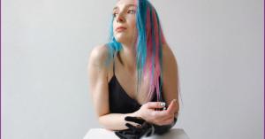 Fotografía de una mujer con una protesis negra en su brazo izquierdo mirando a la izquierda