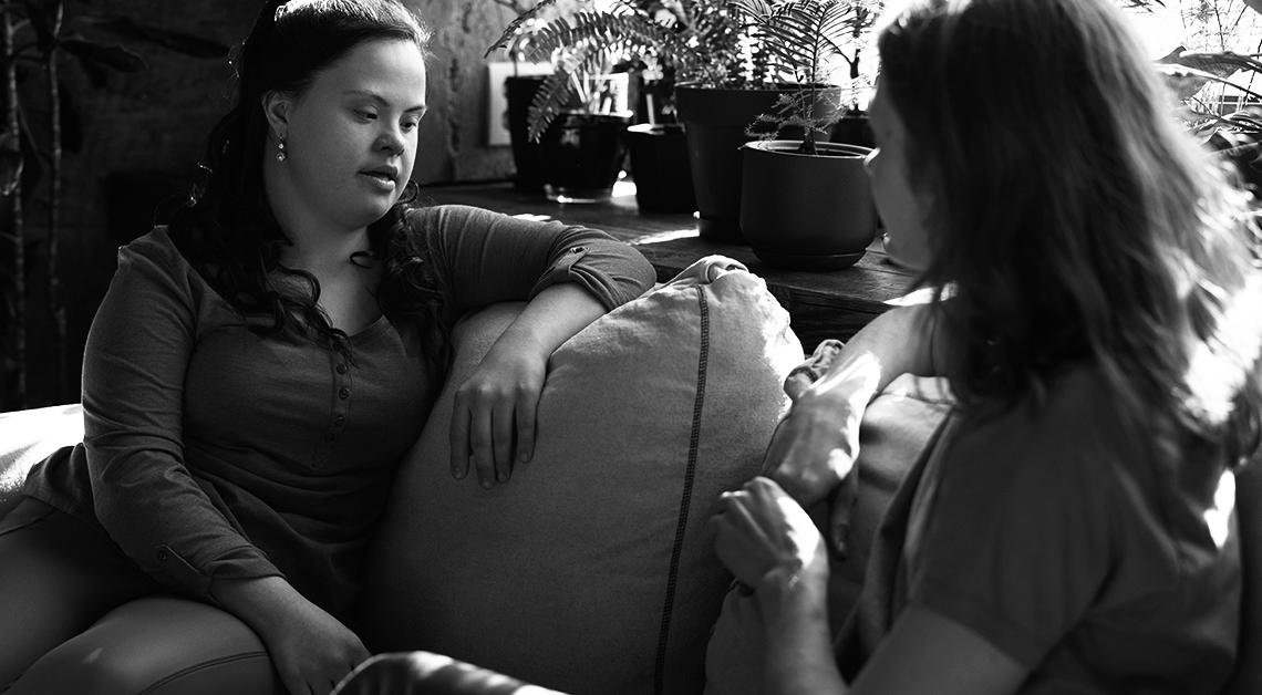 Fotografía de una mujer con sindrome de down sentada en en sillon junto a una mujer
