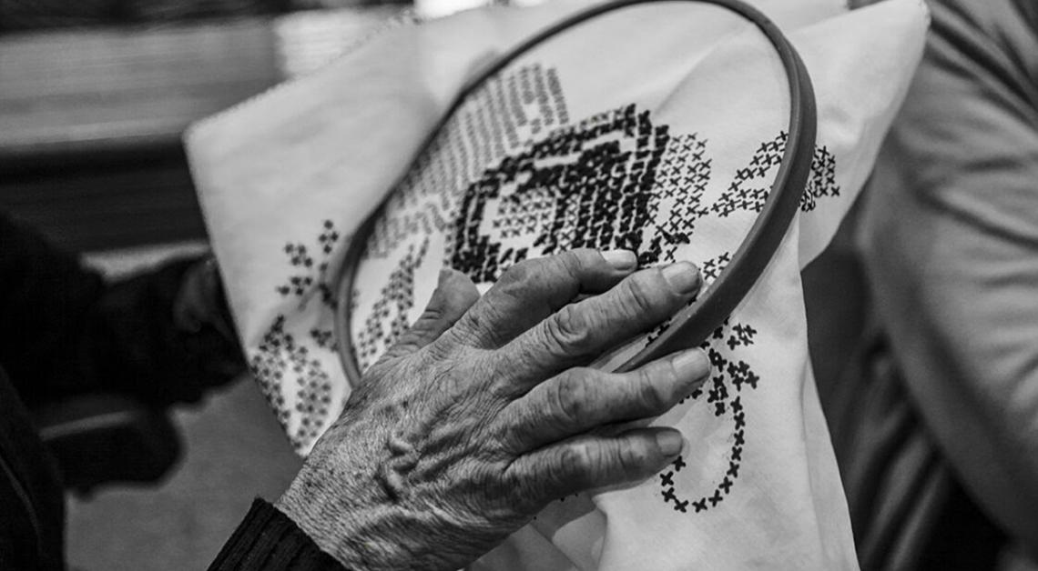Fotografía de la mano arrugada de una mujer tejiendo.