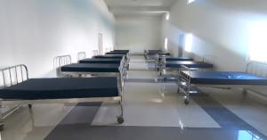 Fotografía de uno de los pabellones de un hospital psiquiatrico con una linea de camas vacias
