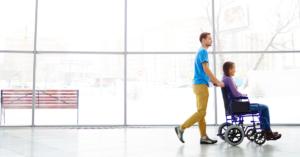 Fotografía de un hombre ayudando a una mujer en silla de ruedas empujándola en un edificio.