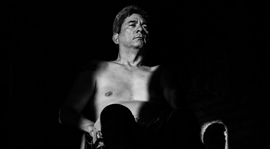 Fotografía en blanco y negro de un hombre en silla de ruedas, en donde se alcanza a ver parte de su pecho y su cara, tiene una mirada desafiante pero parece esconderse en la sombra