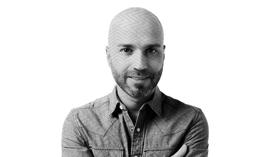 Fotografía con efecto blanco y negro y un patrón de líneas transparentes sobre el rostro Gabriel Bauducco, un hombre de mediana edad con calvicie y barba en su rostro, aparece sonriendo, cruzando los brazos, utilizando una camisa.