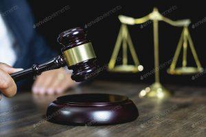 Fotografía en donde aparece una mano de juez sosteniendo un mallete y detrás, en segundo plano, se muestra la balanza de justicia.
