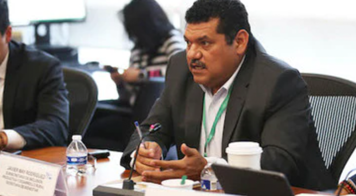 Fotografía del Senador Javier May sentado detrás de un escritorio. Esta usando un traje negro con una camisa blanca, tiene las manos sobre el escritorio y sostiene una pluma con su mano derecha. Detrás de el una mujer trabajando.