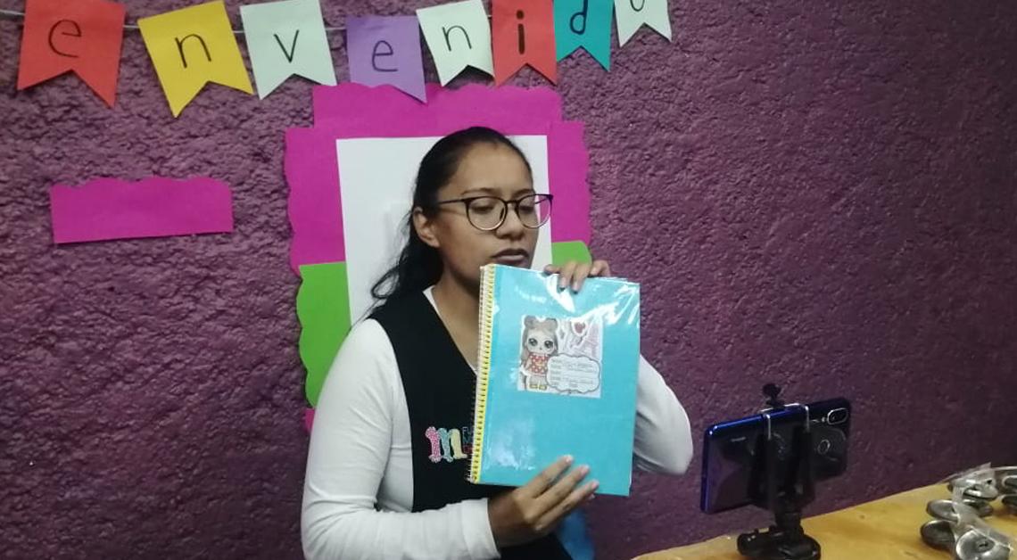 Fotografía de una maestra parada dando su clase. Sostiene un cuaderno en las manos.
