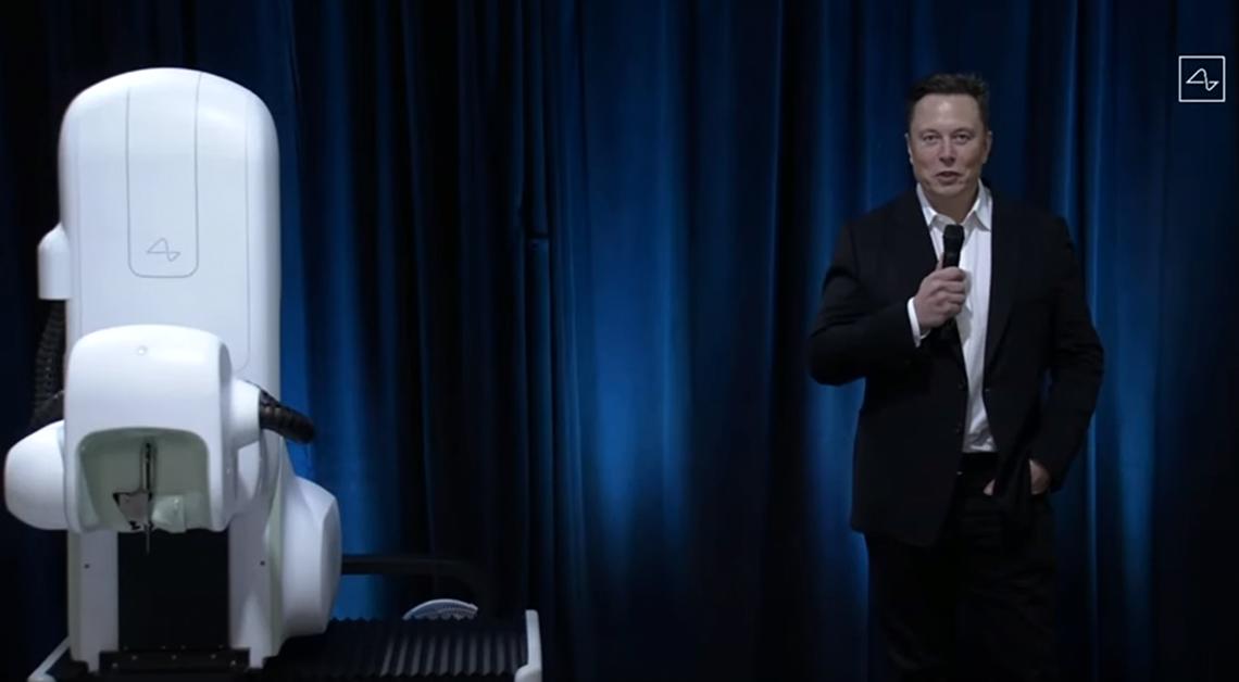 Fotografía de cuerpo completo de Elon Musk, en la fotografía Elon viste un traje negro con una camisa blanca y corbata negra, sostiene en su mano derecha un micrófono, a la derecha de Elon está una de las partes del neurolink, es una maquina grande color blanco. Detrás de ellos una cortinilla color azul.