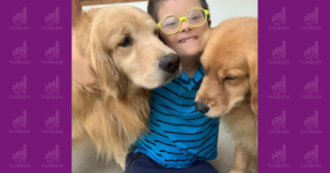 Fotografía de un niño con sindrome de down abrazando a dos perros.