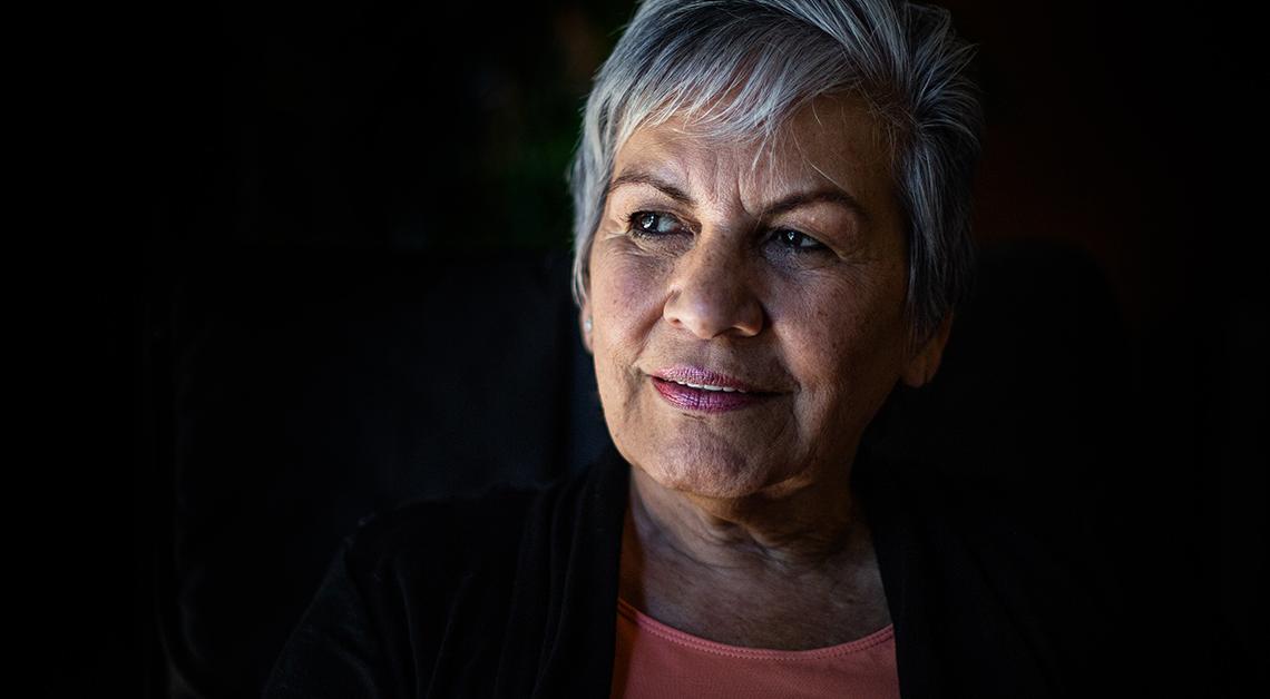 Fotografía de mujer con vista hacia la izquierda en un fondo negro
