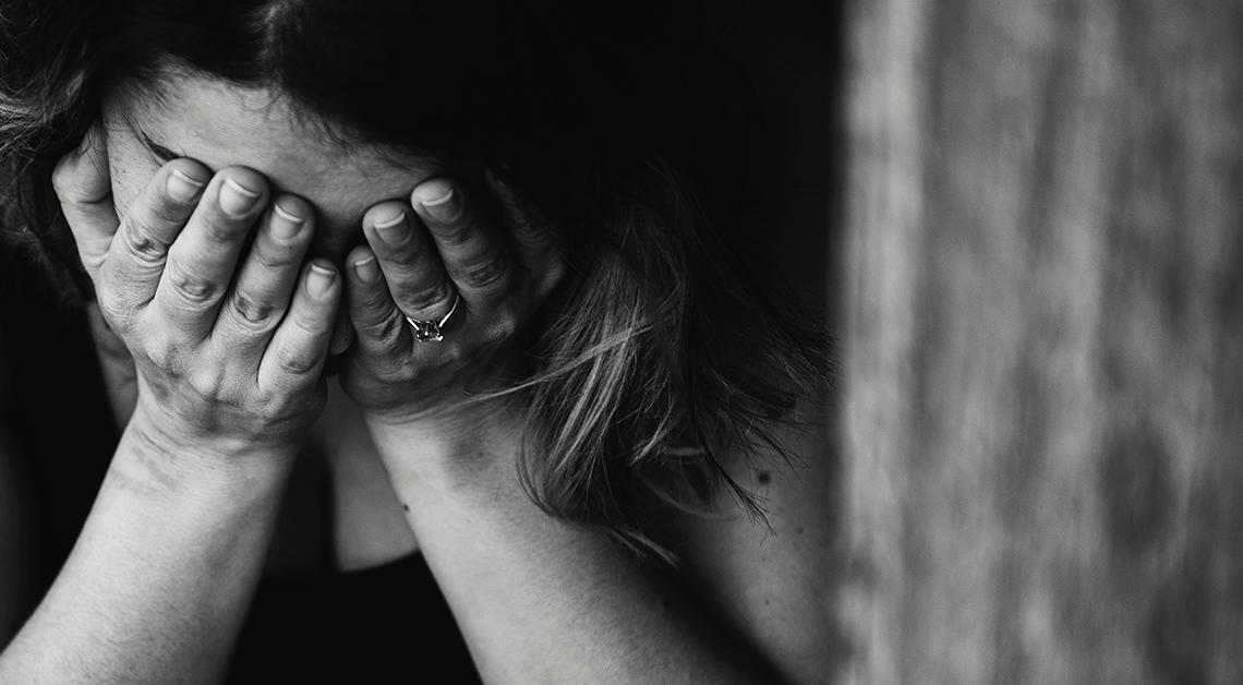 Fotografía en blanco y negro de una mujer con las manos en su rostro.
