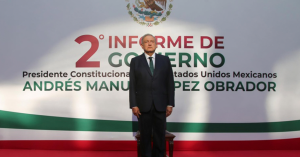 Fotografía de Andres Manuel López Obrador parado frente al estrado mientras da el segundo informe de gobierno, detrás de el en letras grandes el título segundo informe de gobierno.