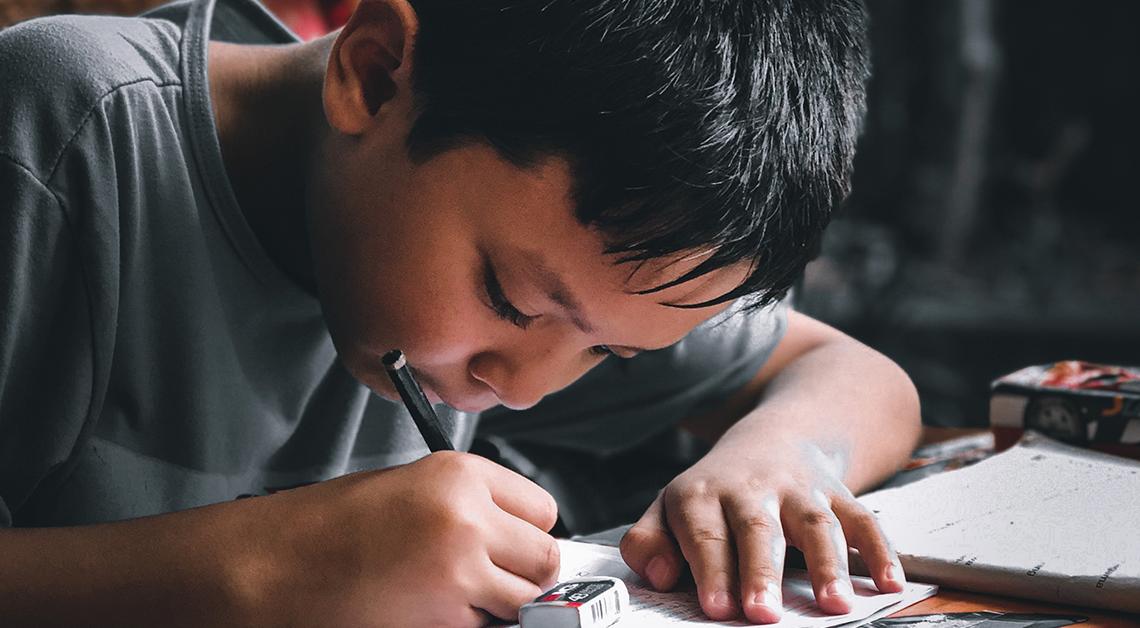 Imagen ilustrativa de un niño escribiendo.