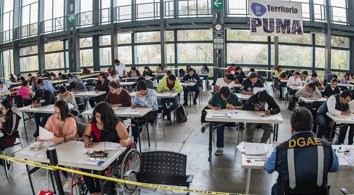 Fotografía de uno de los grupos de estudiantes presentando su examen para ingresar a la UNAM, al frente una mujer en silla de ruedas vestida de rojo, detras de ella una fila de 4 escritorios, cada uno con 2 estudiantes, todos viendo su hoja de examen con un lápiz en la mano.