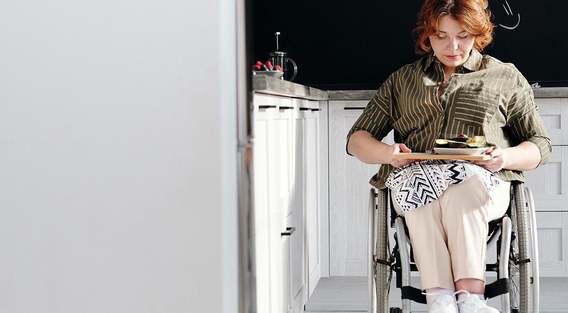 Imagen ilustrativa de una mujer vistiendo una blusa verde y pantalón blanco, sentada en una silla de ruedas..