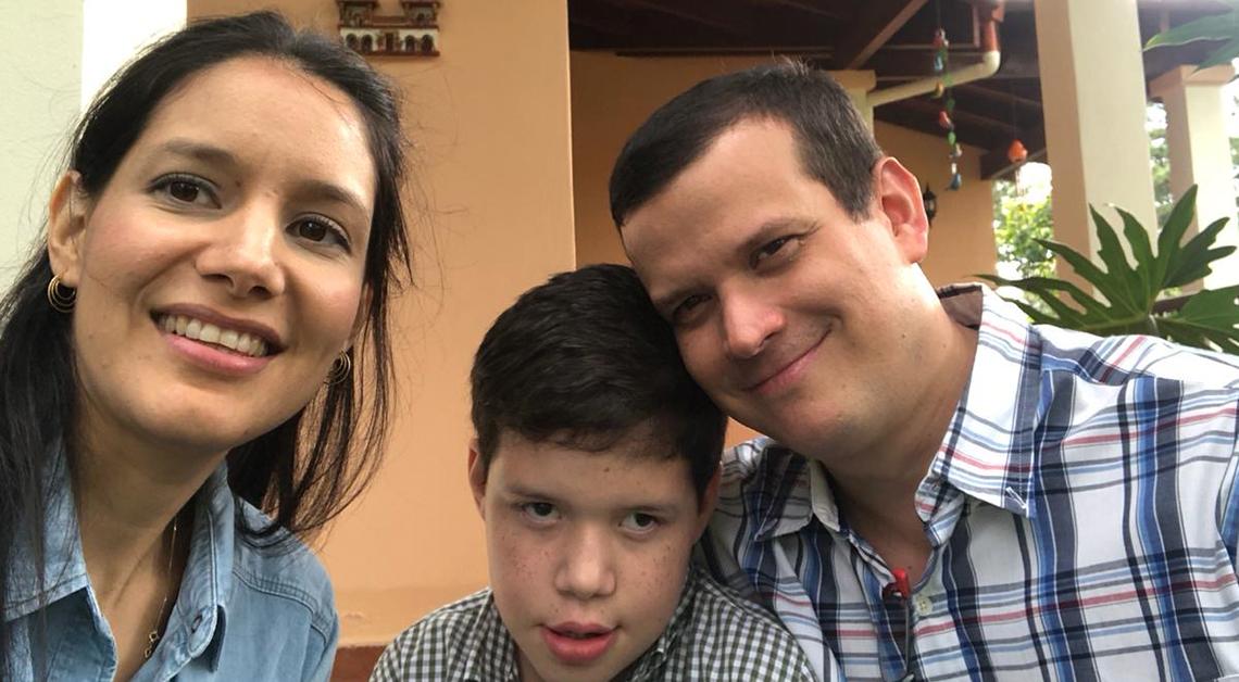 Fotografía de Di con sus papás, Karola y Dieter. En la fotografía los tres están sonriendo, su papá usa una camisa de rayas y su mamá una camisa de mesclilla azul, Di tiene una camisa de cuadritos, todos ven a la cámara.