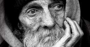 Fotografía en blanco y negro del rostro de un hombre con la mano en su barbilla.