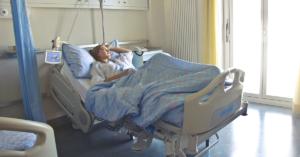 Fotografía de una mujer recostada en una cama de hospital, esta cubierta hasta la cintura con una cobija azul, tiene un brazo en el pecho y el otro en la cabeza, esta viendo hacia la izquierda.