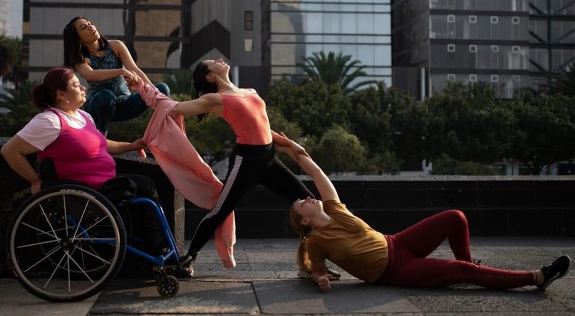 Fotografía de una coreografía. De izquierda a derecha, una mujer en silla de ruedas con una blusa rosa, junto a ella una mujer agachada agarrando un brazo de otra mujer frente a ellas que esta vestida con blusa rosa y un pantalón negro.