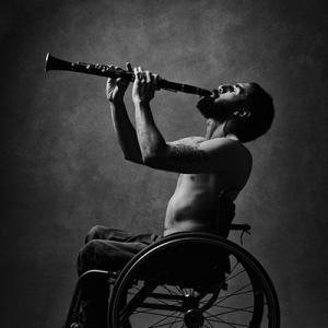 Fotografía de un hombre en silla de ruedas tocando el clarinete.
