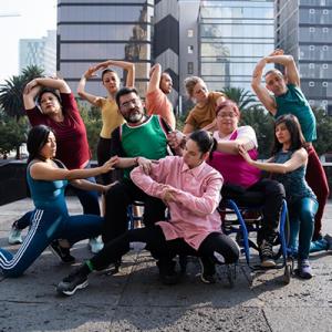 Fotografía de una coreografía, en el centro dos personas en silla de ruedas, junto a ellos el resto del elenco.