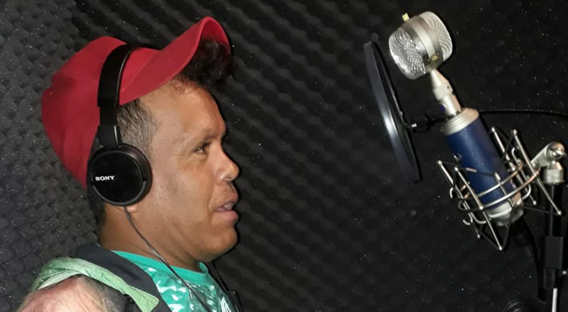 Fotografía del rostro de Sergio de perfil, está usando una gorra roja y frente a el un micrófono.