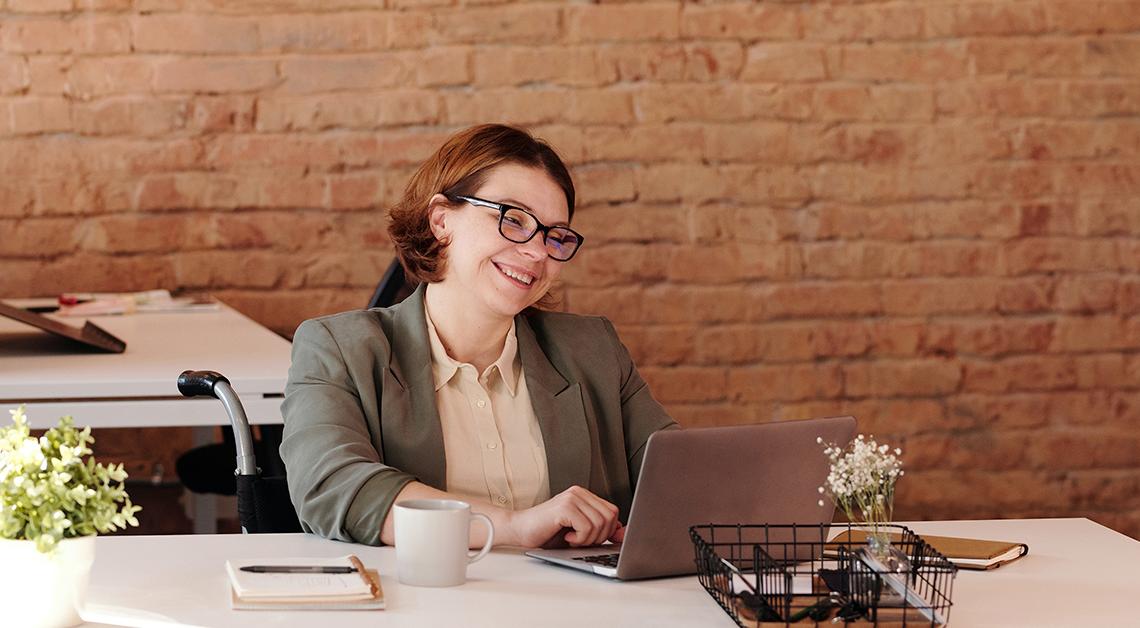 Fotografía de una mujer frente a una computadora sonriendo.