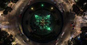 Fotografía aerea del angel de la independencia con tres luces verdes a su alrededor.