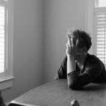 Fotografía en blanco y negro de un hombre sentado detrás de una mesa cubriendo su rostro con su mano.