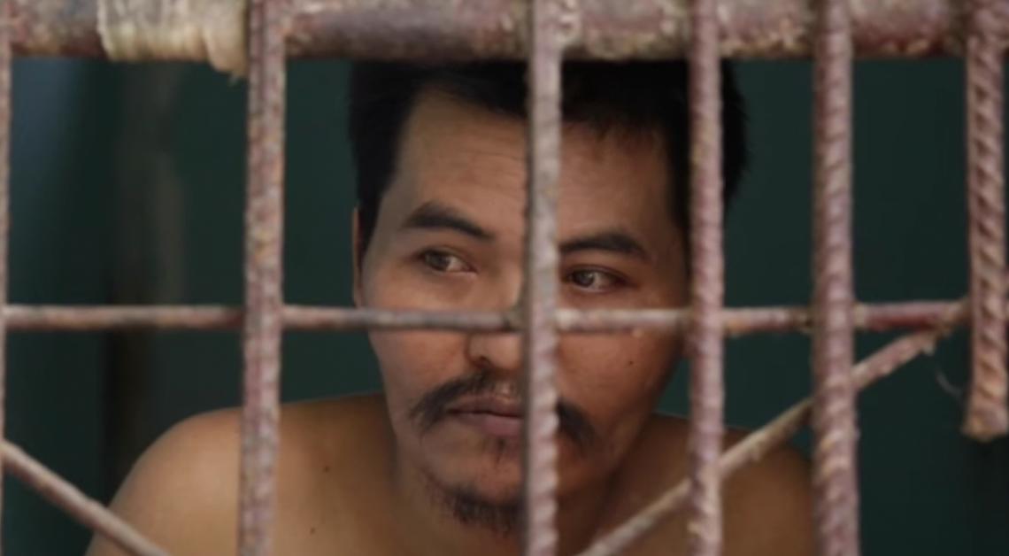 Imagen ilustrativa del rostro de un hombre detrás de unas barras de metal.
