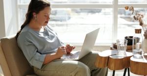 Fotografía de una mujer con sindrome de down frente a una computadora.