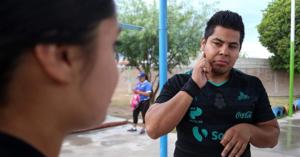 Imagen ilustrativa de un hombre hablando con lengua de señas, viste una playera deportiva.