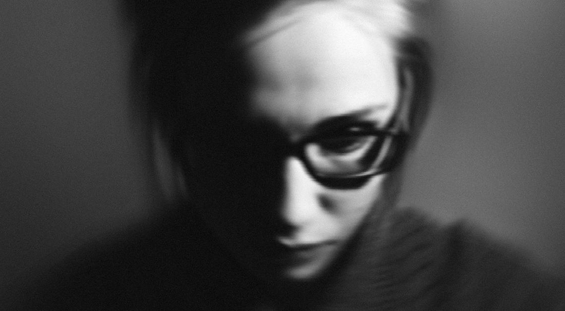Rostro de una mujer con el cabello recogido y lentes negros.