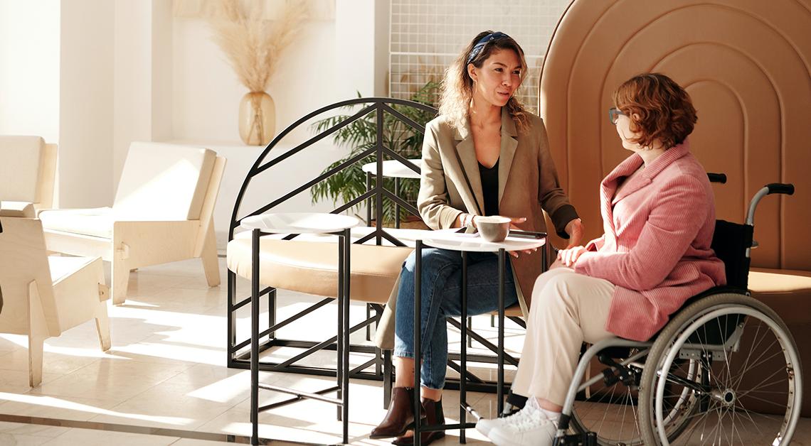 Fotografía de una mujer sentada en silla de ruedas frente a una mesa, a su derecha una mujer, viste un saco color cafe, están sentadas en una cafetería.
