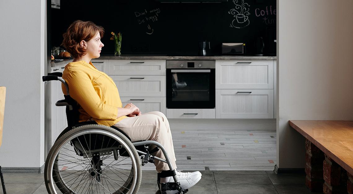 Fotografía de perfil de una mujer en silla de ruedas, detrás de ella su cocina y frente a ella su ventana.