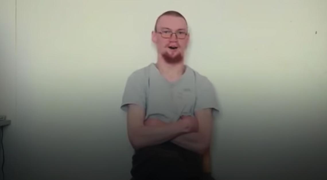 Fotografía del joven ruso sentado viendo a la cámara usando una playera gris.