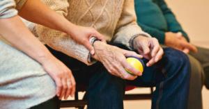 Fotografía de las manos de un adulto mayor con una pelota en la mano izquierda mientras las manos de una mujer están recargadas en su antebrazo.