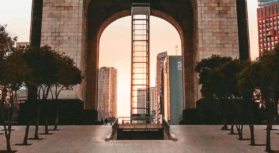 Fotografía de la base del monumento a la revolución, a los lados arboles y en el centro la entrada al monumento.