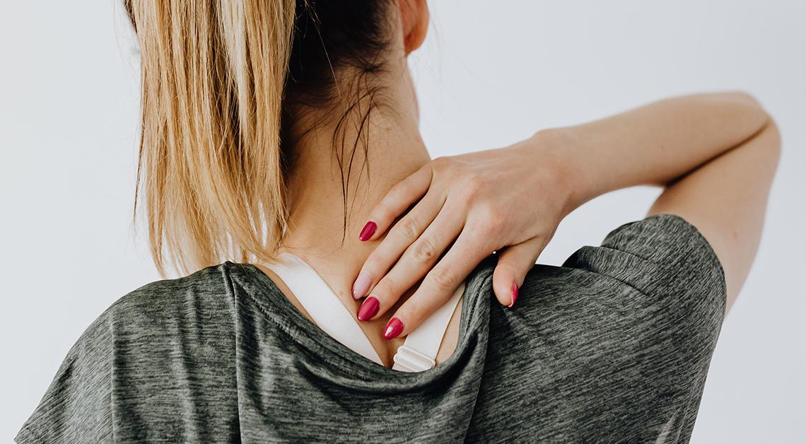 Fotografía de la espalda de una mujer donde tiene su mano sobre su cuello.