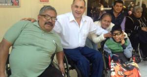 Fotografía de 4 personas sentadas en silla de ruedas. De izquierda a derecha, el primero es un hombre con una playera azul y lentes, junto a el un hombre con camisa blanca y pantalon de mezclilla, junto a ellos un niño sonriendo con lentes y una chamarra verde y detras de el una señora con sus manos en los hombros del niño.