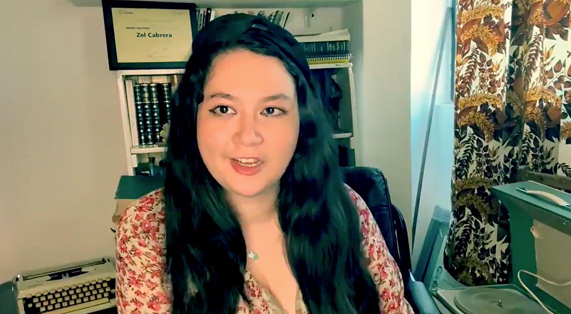 Fotografía del rostro de Zel Cabrera con el cabello suelto y una blusa color cafe, detras de ella un librero.