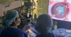 Fotografía de dos doctores de espaldas con una bata y gorro color azul, ven una pantalla donde se ve un ojo.