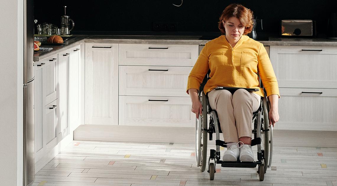 Fotografía de cuerpo completo de una mujer en silla de ruedas viendo hacia abajo, tiene una blusa color amarillo y un pantalón café.